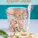 A Kilner jar containing Russian salad made with chickpeas, chopped potatoes, peas, carrots. There is a blie and white spoon standing against the jar and the sceen is propped with chips and a bunch of dill. Text overlay reads Healthy Veggie Russian Salad.