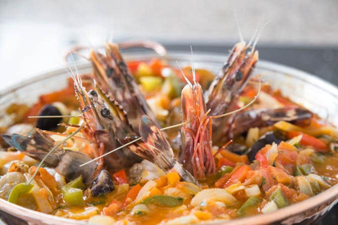 Raw prawns arranged in a pepper, onion and tomato sauce in a Portuguese Cataplana pan