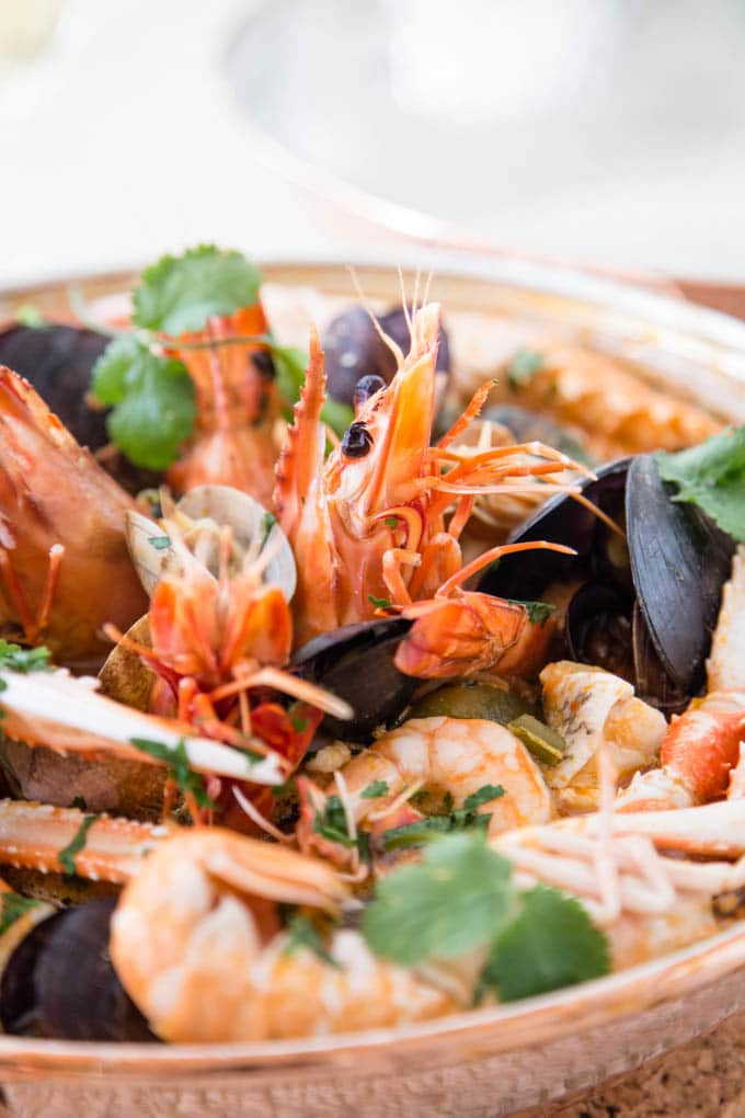 Close up of a traditional Traditional Portuguese cataplana pan filled with a sea food cataplana. Prawns, mussels and other seafood with a sprinkling of coriander