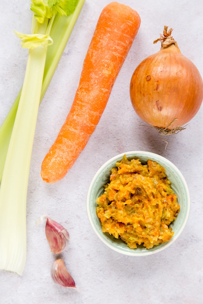 A picture from above of a small dish of soffritto paste together with the main ingredients: celery, garlic, carrot and onion.