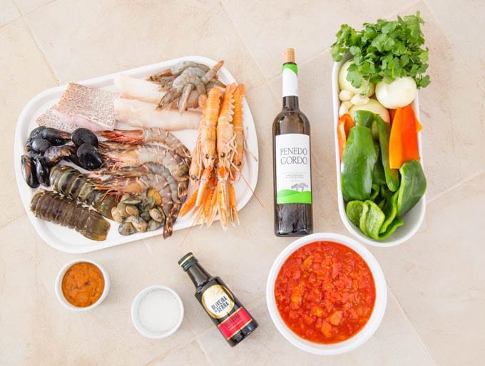 Ingredients for a Portuguese Cataplana viewed from above. A seleciton of mixed seafood, fresh red and green peppers, onions, garlic and coriander, a bowl of canned tomoatoes, a bottles of wine and olive oil, salt and a bowl of lobster sauce.