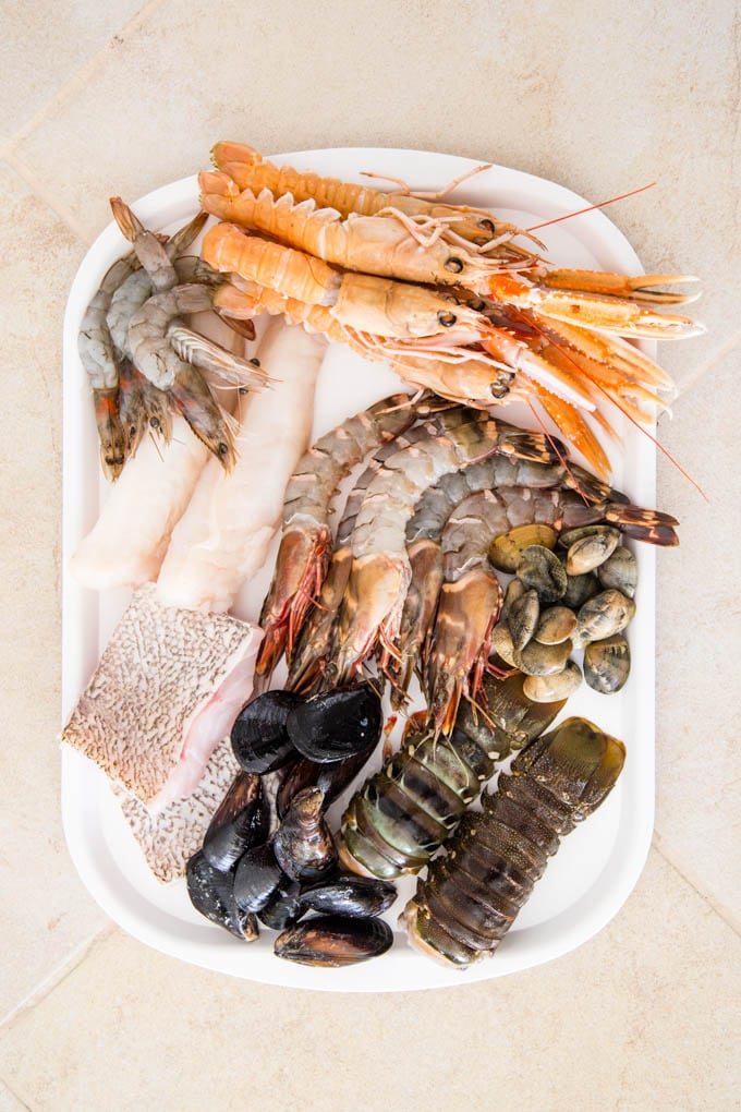 Plate of fresh seafood containing tiger prawns, crawfish, lobstertails, mussels and fish, viewed from above