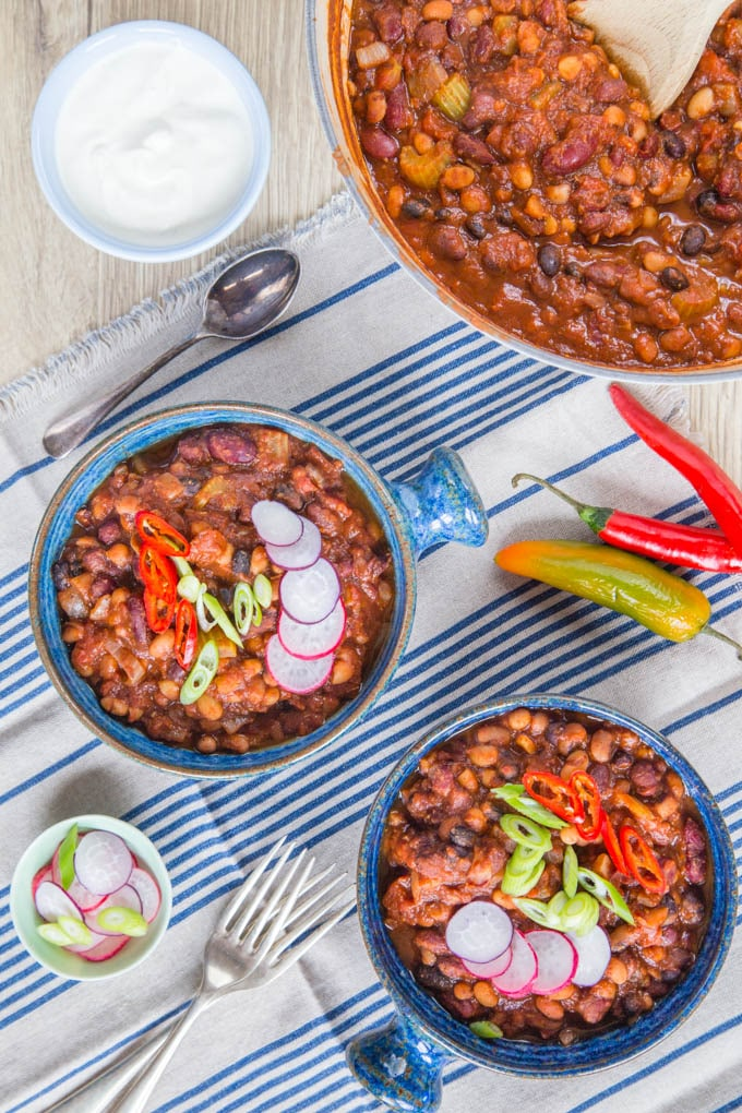 two servings of vegan 5 bean chilli topped sliced chillies, radishes and spring onions served in blue serving bowls together with a white casserole dish of chilli