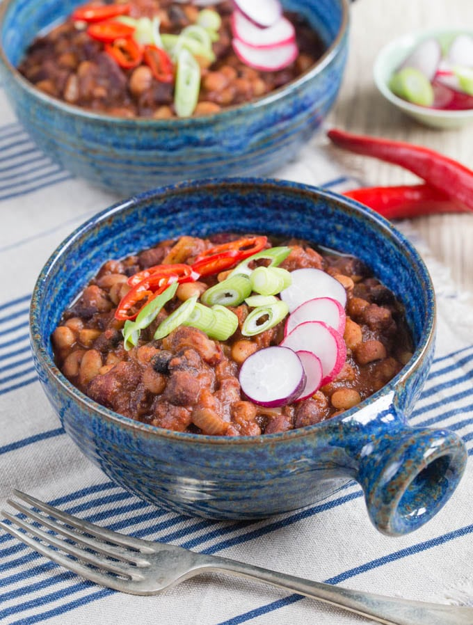 Delicious vegetarian 5 bean chilli with added crunch and heat from radishes, fresh chillis and spring onions served in deep blue bowls