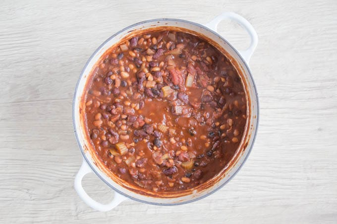 A white casserole dish full of cooked of vegan 5 bean chilli.