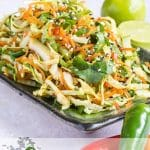 "An oblique shot of a green rectangular plate heaped with Asian coleslaw. Some chilis in the foreground, and an out of focus lime behind. - text overlay reads ""asian slaw"""