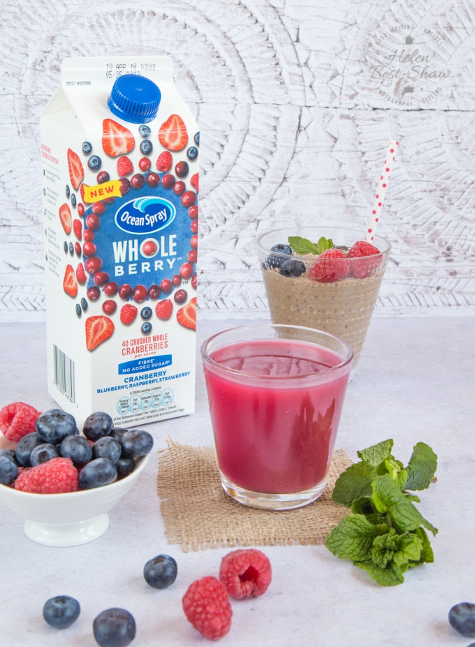 A carton of Ocean Spray Whoe berry juice ,a glass of dark red juice, a bowl of berries and fresh mint in the foreground