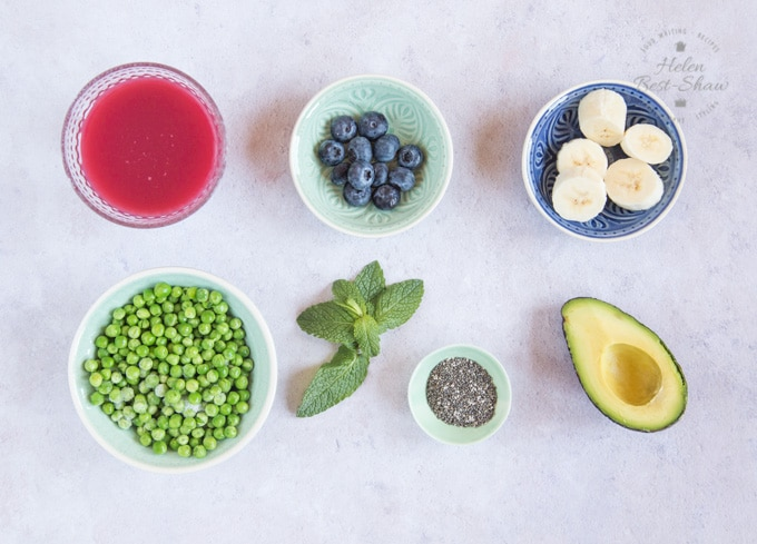 A top down shop of cranberry juice, blueberries, banana, avocado, chia seeds, mint and peas each arranged in bowls: the ingredients for Cranberry smoothie with pea and avocado.