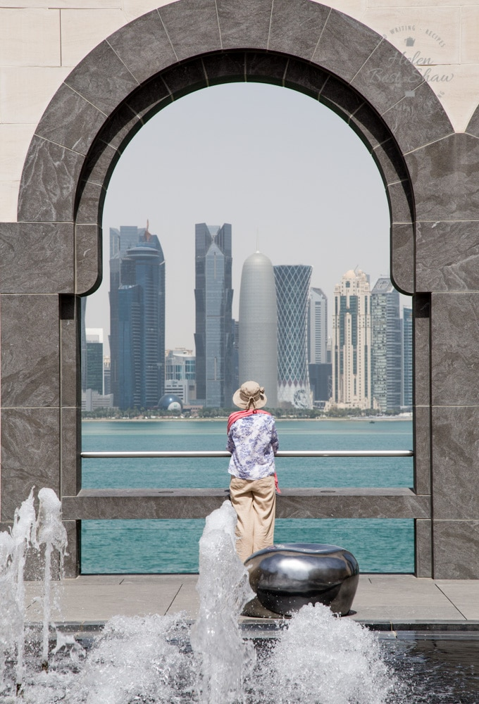 View of the moder skyscrapers of Doha seen from an archway at the museum of Islamic art. Fountains in the foreground.