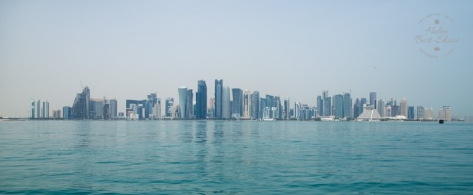 The futuristic skyline of Doha, with fantastically designed modern skyscrapers in front of an azure blue sea