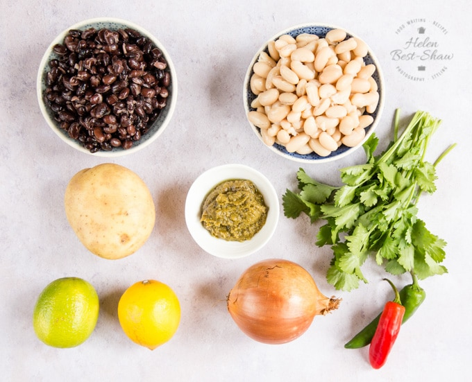 The ingredients for green Thai curry spicy bean burgers. Two bowls of beans, a potato, an onion, two chilis, green thai curry paste in a small bowl, fresh coriander leaves, and a lime and a lemon.