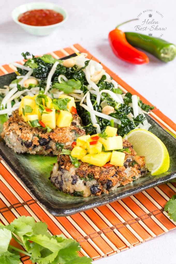 Two spicy bean burgers on a rectangular plate, topped with mango salsa and accompanied by a green leaf and beansprout salad, and a slice of lemon.