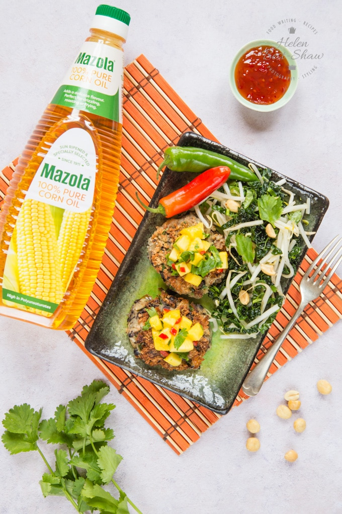 A rectangular plate holding 2 spicy bean burgers and salad. A bottle of Mazola corn oil is placed next to the plate.