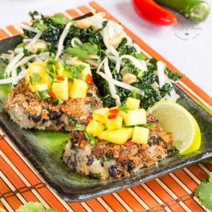 A close up of two spicy bean burgers on a rectangular plate, topped with mango salsa and served with a green leaf and beansprout salad.