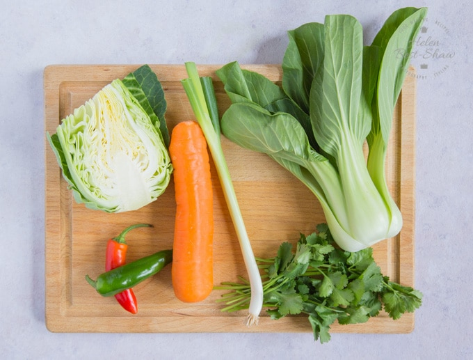 The whole, raw ingredients of Asian coleslaw, laid out on a wooden board. Hipsi, pak choi, carrot, chili, and coriander