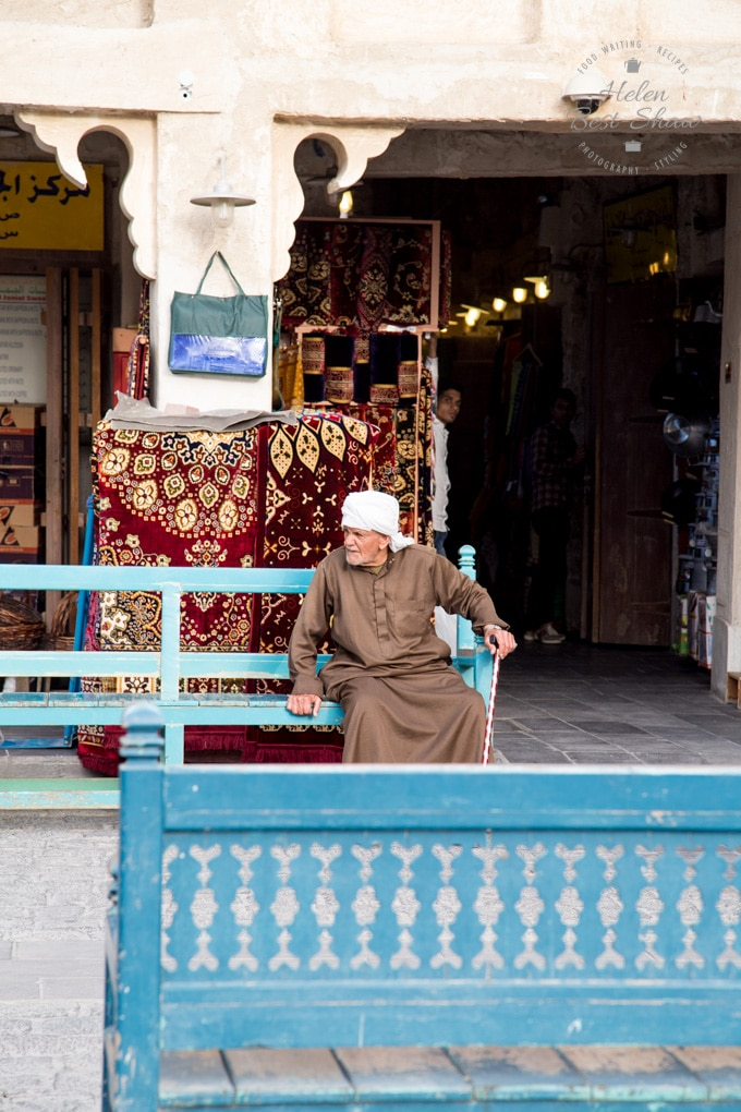Traditionally dressed Qatari man sitting on a blue bench outside a shop in a souk