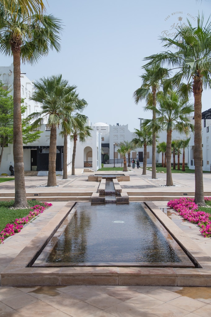 A waterfeature surrounded by pink flowers, palm trees and white villas