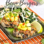 Two Thair green curry bean burgers on green plate. each burger is topped with mango salsa and they are served wtih a beansprout salad.