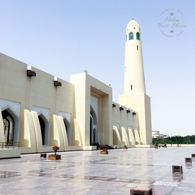 Outside of the Grand Mosque Doha, with white walls and a plain minaret