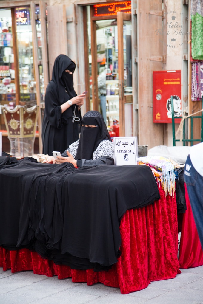 Veiled woman at a stall in the Souk Waqif, Doha