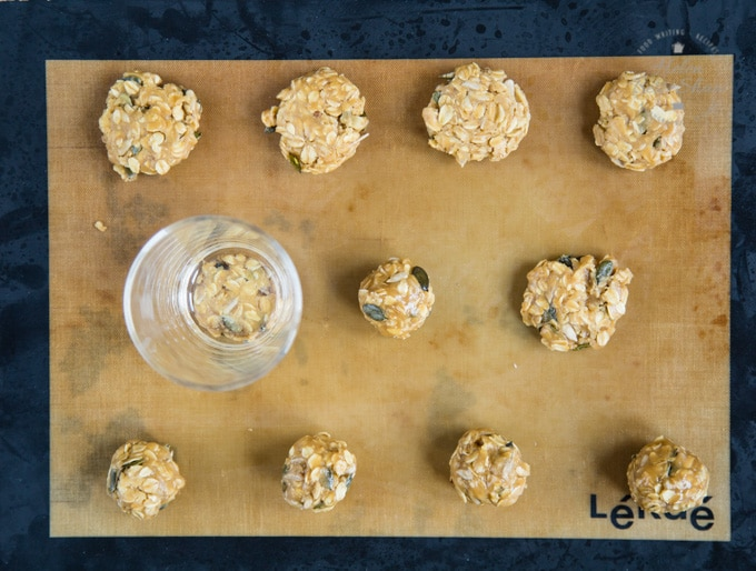 Before baking: balls of dough for easy seeded vegan oat cookies on a baking sheet. One row has been flattened with a glass.
