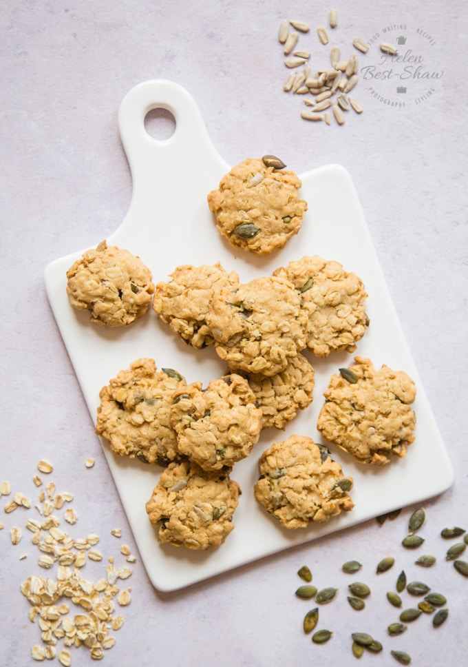 Eleven golden easy seeded vegan oat cookies laid out randomly on a rectangular white platter.