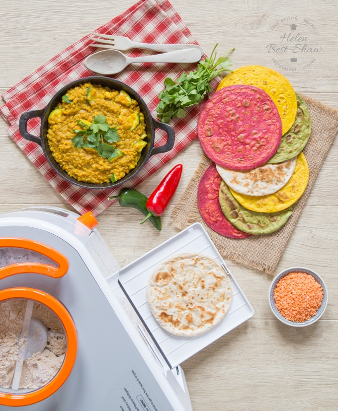 A top down view of the rotimatic roti maker, laid out with some coloured rotis and a dish of courgette daal.