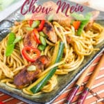 a plate of Chicken Chow Mein, made with egg noodles and full of green courgettes, mange tout, red peppers and chicken pieces. The photo shows a red chilli and pair of chopsticks. Text overlay reads Easy Chicken Chow Mein.