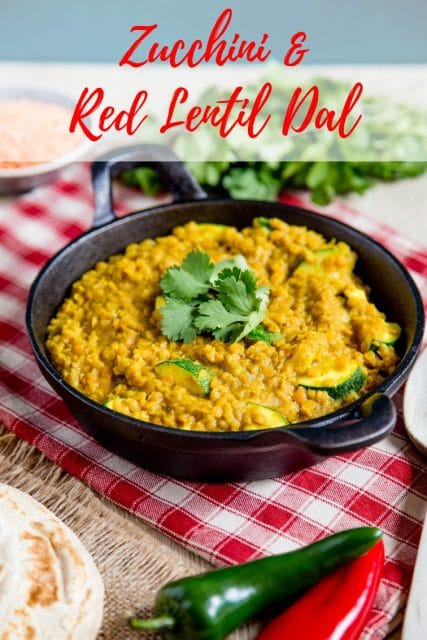 A round black cast iron dish contains golden courgette and lentil dal which is topped with fresh coriander. The table is set with a red and beige checked cloth and there are fresh red and green chillis, flatbreads and a bunch of coriander. Text overlay reads Zucchini and red lentil dal