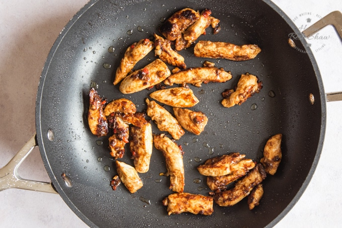 Pieces of chicken frying in a large, deep frying pan for chicken chow mein.