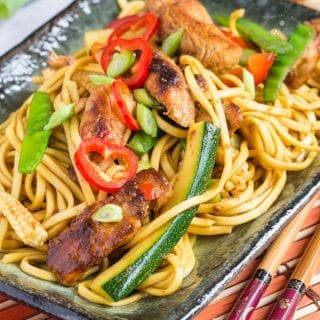 A close up on a rectangular plate of easy chicken chow mein. Noodles, chicken pieces, batons of courgette, mange tout peas and slices of chili can all be seen.
