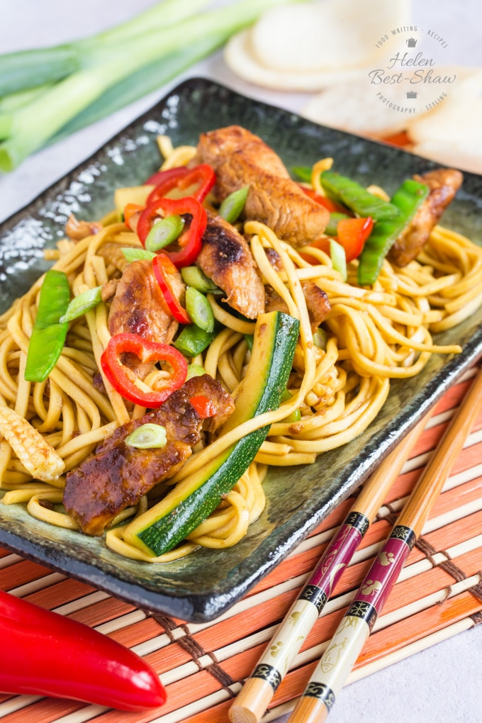 Chinese chow mein with chicken, courgettes, mange-tout peas, slices of chili and egg noodles on a plate. Chopsticks, whole chili and whole spring onions and prawn crackers can be seen on the table.