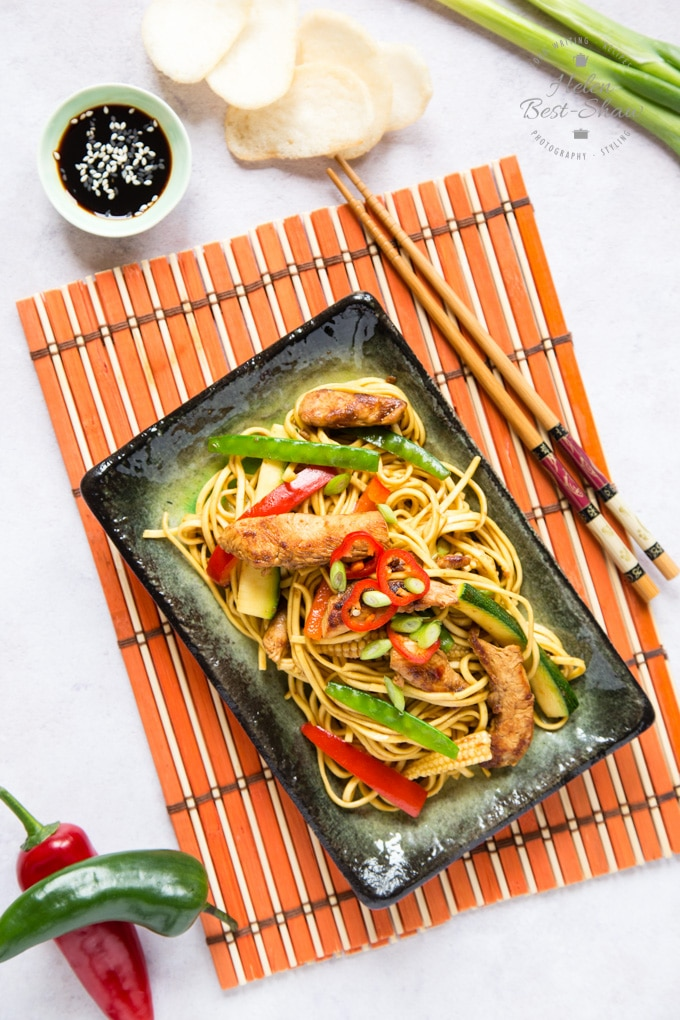 A rectangular plate of chicken chow mein, with green mange-tout peas, red bell peppers and slices of chili, on a bamboo mat. Chopsticks, prawn crackers, whole chilies and spring onions surround the plate.