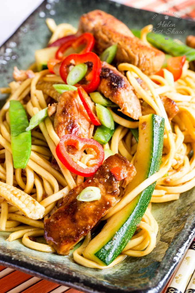 Close up on a plate of delicious chicken chow mein that's ready to eat. Pieces of chicken, batons of courgette, egg noodles and slices of chili can be seen.