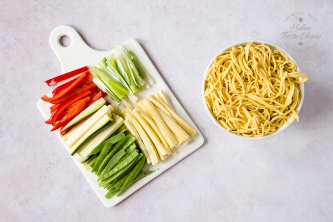Prepared ingredients for chicken chow mein: baby corn, mange-tout peas, courgettes sliced into batons and sliced red bell peppers and spring onions on a square porcelain plate, alongside a bowl of egg noodles.