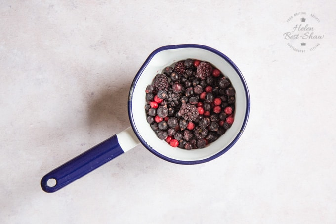 A saucepan of frozen fruit for a mixed berry compote.