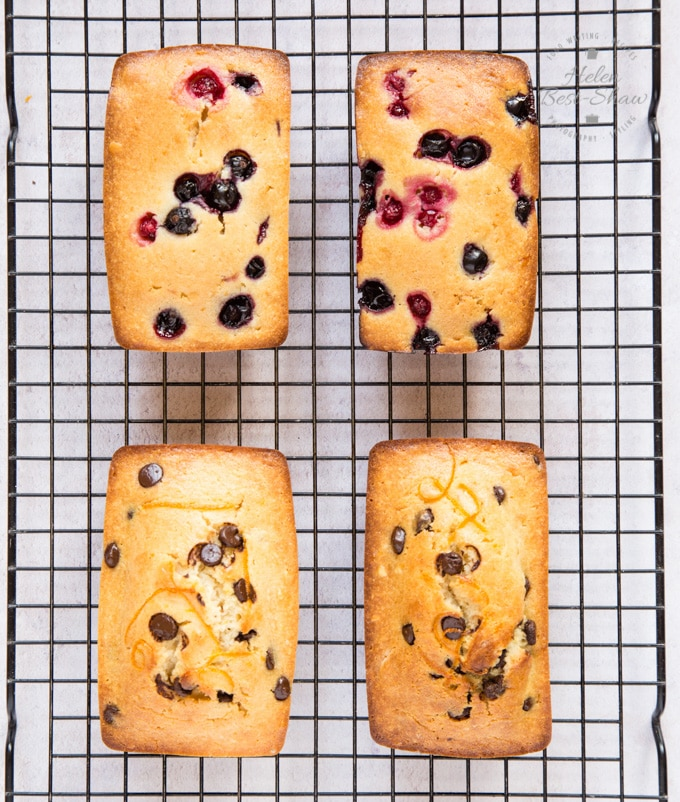 A top down shot of four yogurt mini loaf cakes on a cooling rack. Two made with berries, two with chocolate chips.