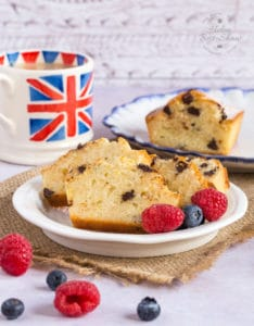 Slices of yogurt mini loaf cakes on a side plate. Raspberries and blueberries in the foreground, and a union jack cup of tea in the background.