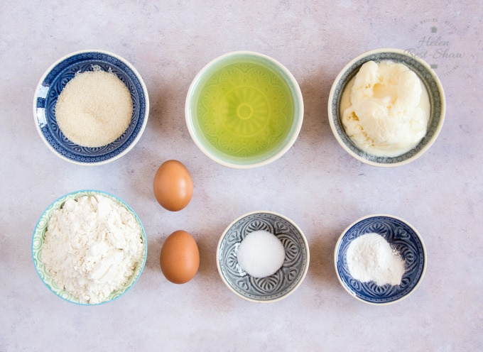 The ingredients for yogurt mini loaf cake batter: sugar, oil, frozen yogurt, flour, salt and baking powder.
