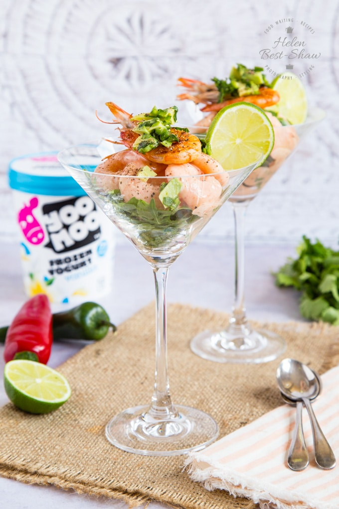 Two cocktail glasses of retro prawn cocktail, standing on a hessian cloth. They are garnished with a cooked prawn and a slice of lime. In the background is a tub of yoomoo yogurt.