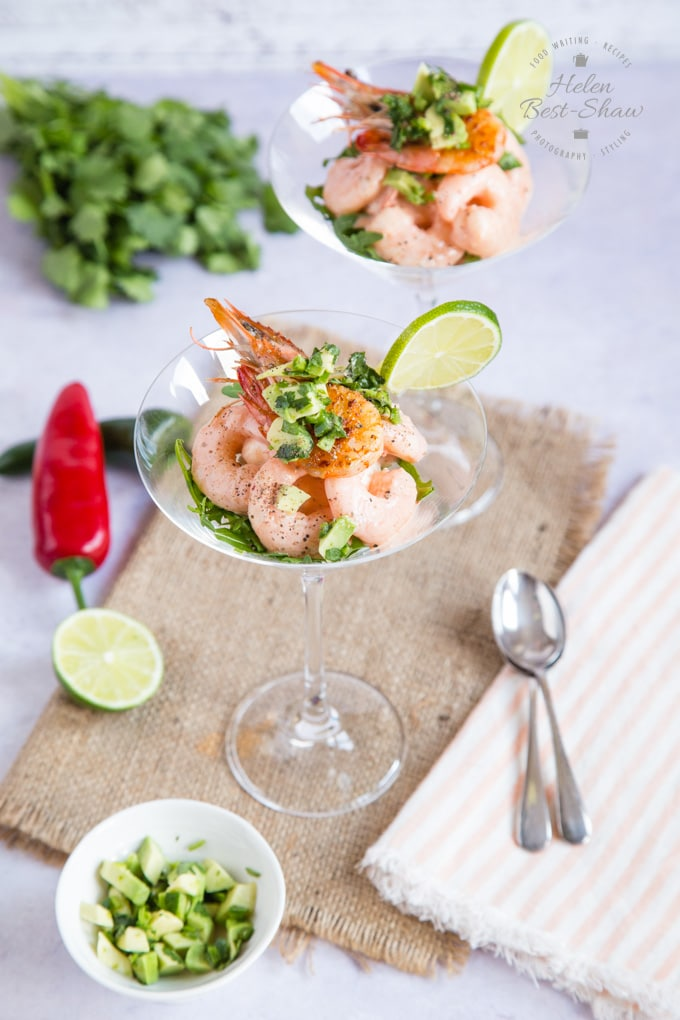 Looking down on two cocktail glasses, with prawns covered in cocktail dressing. Garnished with finely diced avocado, a cooked prawn and a slice of lime.