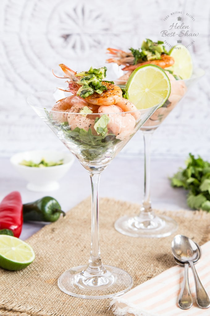 Two cocktail glasses of retro prawn cocktail, standing on a hessian cloth. They are garnished with a cooked prawn and a slice of lime.