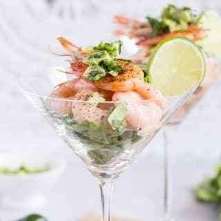 Close up on a retro prawn cocktail, in a traditional cocktail glass. Garnished with a cooked prawn and a slice of lime.