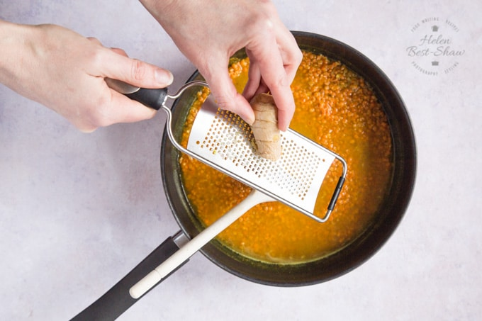 Grating fresh ginger into a frying pan of daal.