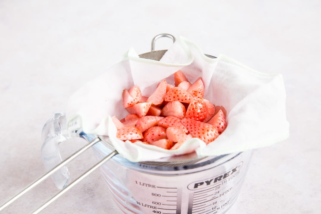 A sieve lined with muslin sits in a glass measuring jug. Nestled in the folds of the cloth are quartered strawberries, pale after steeping in gin.