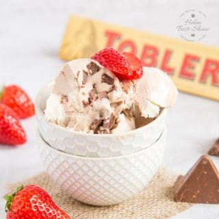 A white textured bowl full of Toblerone Ice Cream surrounded by strawberries and some chunks of chocolate. Also in the photo there is a wooden spoon and a packet of Toblerone Chocolate