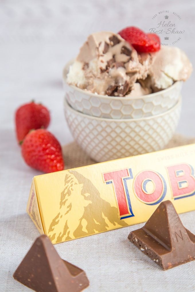 A packet of Toblerone in front of some three ingredient Toblerone ice cream in a bowl. Strawberries and chunks of chocolate in the foreground.