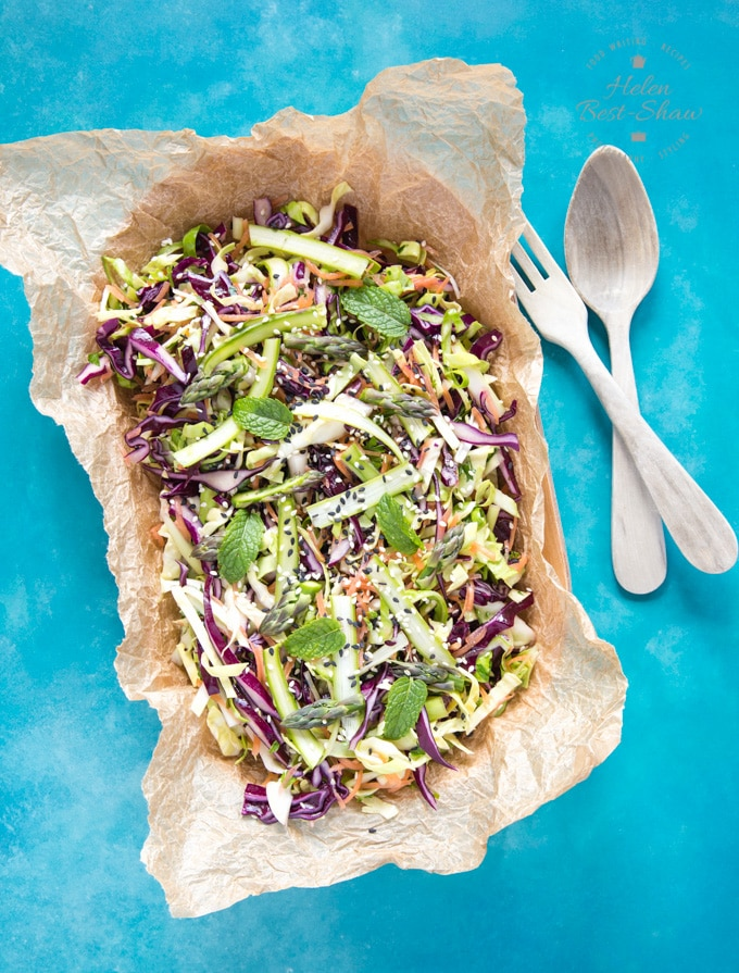A top down view of an oval bowl of asparagus salad, served in greaseproof paper, presented on a blue background. To the side of the dish are a wooden serving spoon and fork.