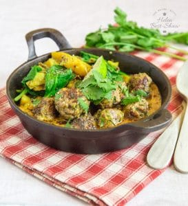 A cast iron dish of beef koftas and sag aloo, on a red and white checked napkin.