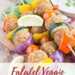 A close up of four falafel and Mediterranean vegetable kebabs on an olivewood board. Text overlay reads Falafel veggie Kebabs